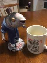 "3D printed fish character, hand painted, the cup is a merchandise test from the same ""universe"""